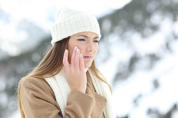 photo of woman in winter touching her face